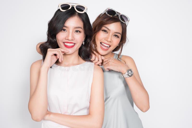 Duas mulheres elegantes nos vestidos agradáveis que estão junto e no havi foto de stock