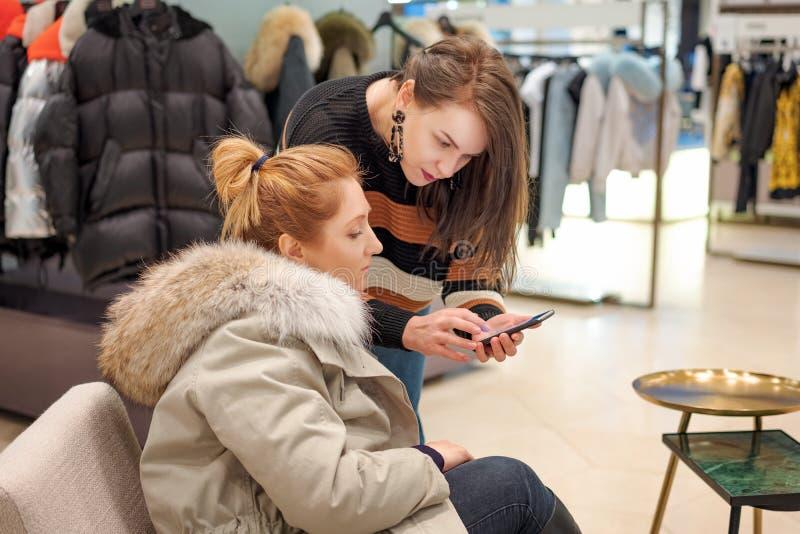 Duas mulheres em uma loja, um estilista e um comprador fotos de stock royalty free