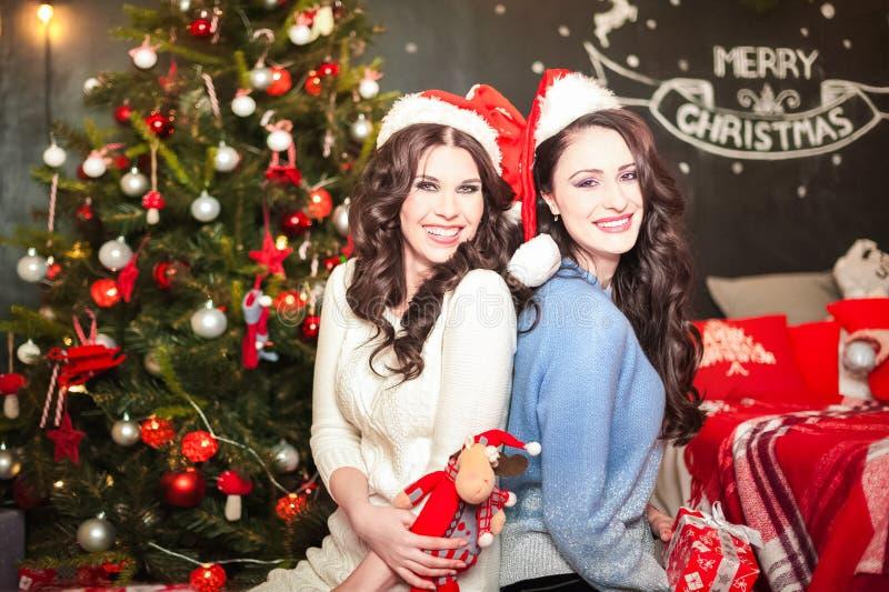 Duas mulheres em uma sala decorada para sorrisos do Natal perto acima Amigas em uma sala com chapéus de Santa Claus fotografia de stock