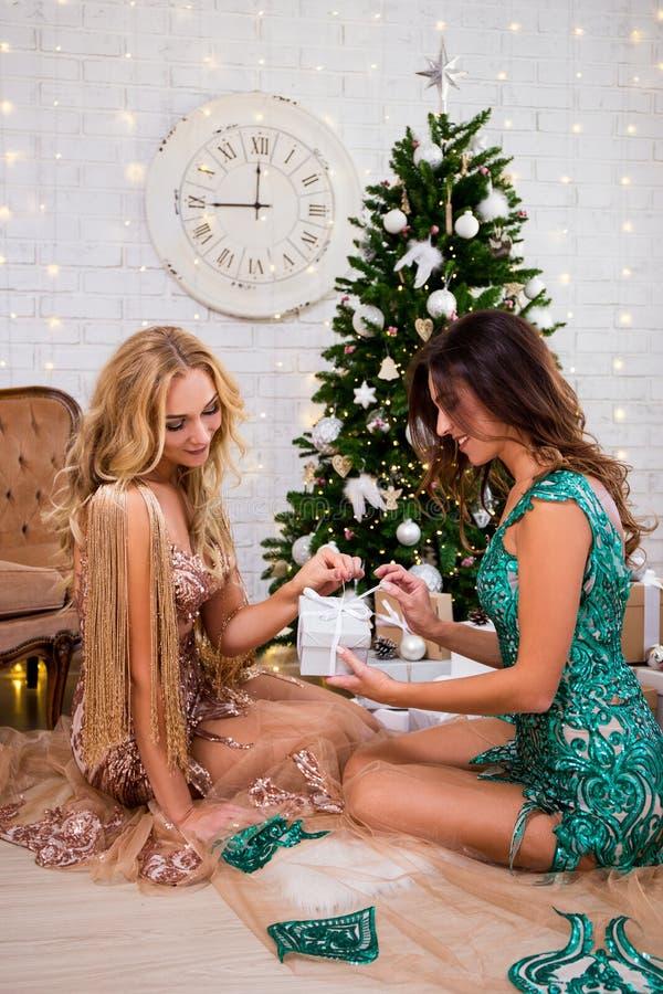 Duas mulheres em vestidos bonitos com as caixas de presente em wi da sala de visitas imagem de stock royalty free