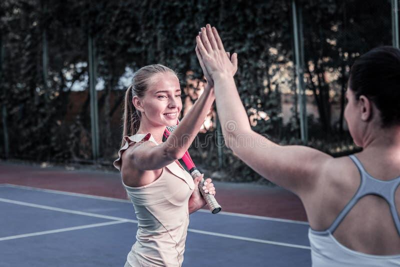 Duas mulheres energéticas que contestam no fósforo do tênis fotografia de stock