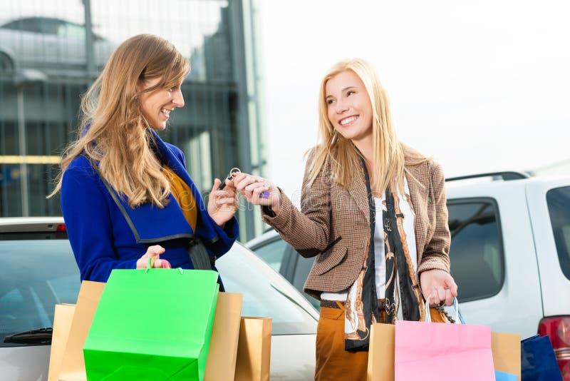 Duas mulheres eram compra e condução para casa imagens de stock