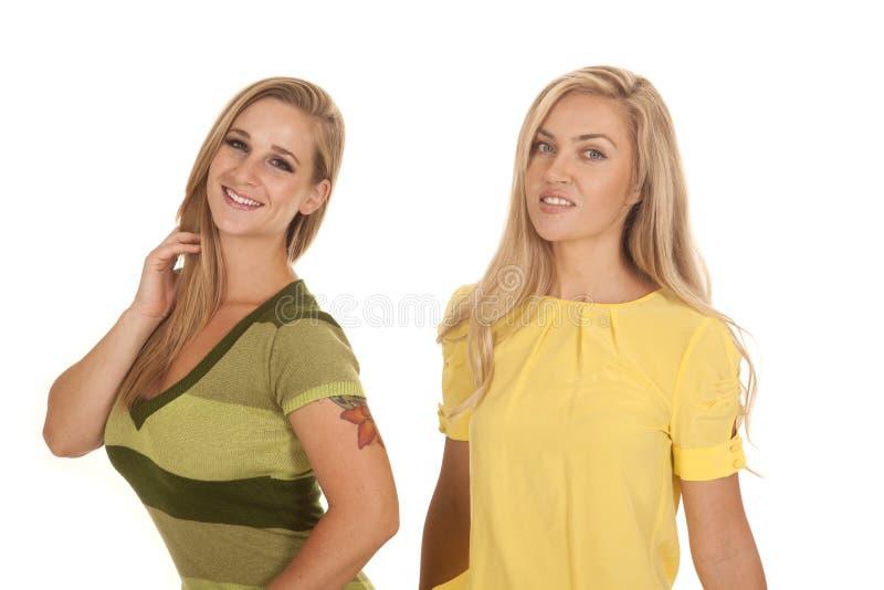 Duas mulheres esverdeiam o sorriso amarelo do suporte foto de stock