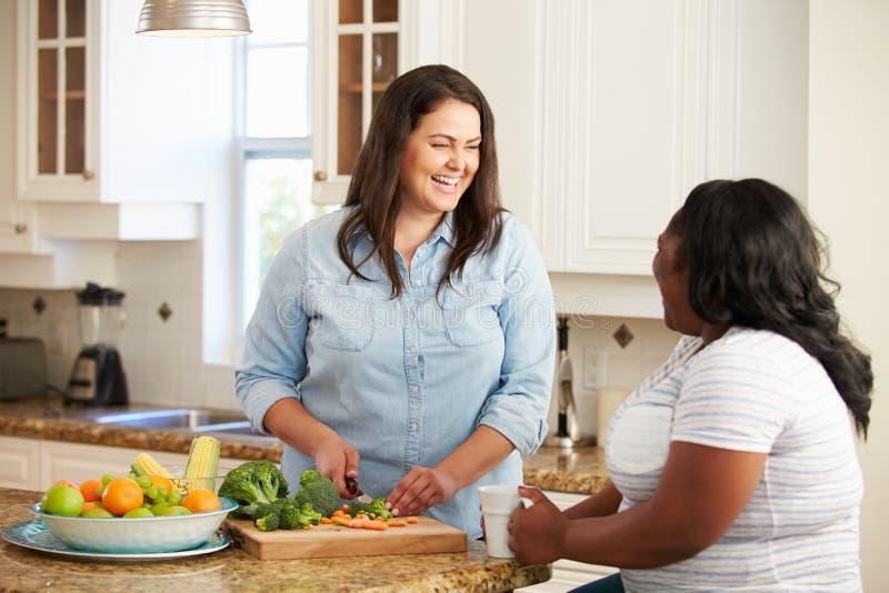 Duas mulheres excessos de peso na dieta que prepara vegetais na cozinha imagens de stock