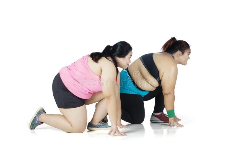 Duas mulheres excessos de peso prontos para ser executado no estúdio fotos de stock