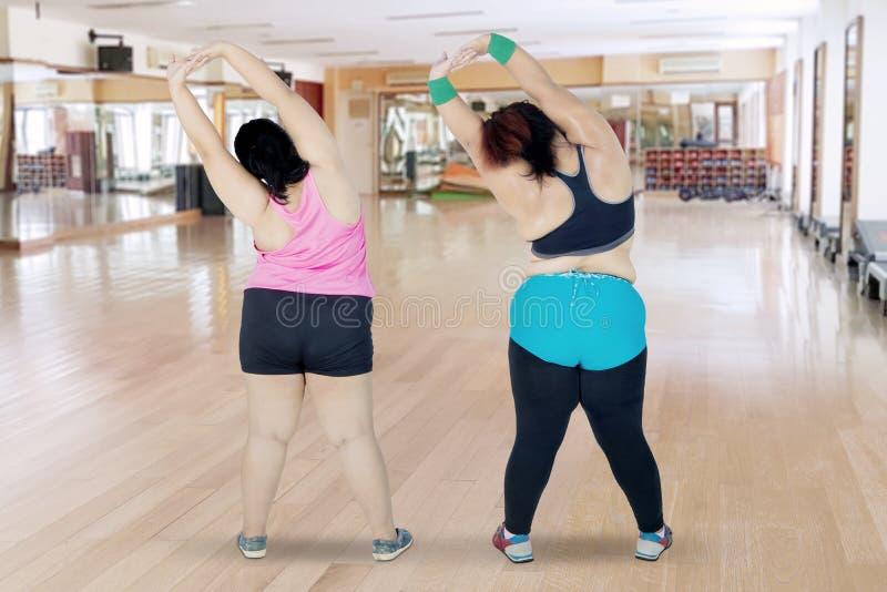 Duas mulheres excessos de peso que esticam as mãos junto fotos de stock