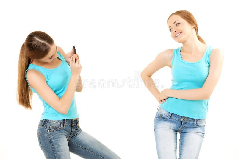 Duas mulheres fazem a foto ao telefone celular imagem de stock