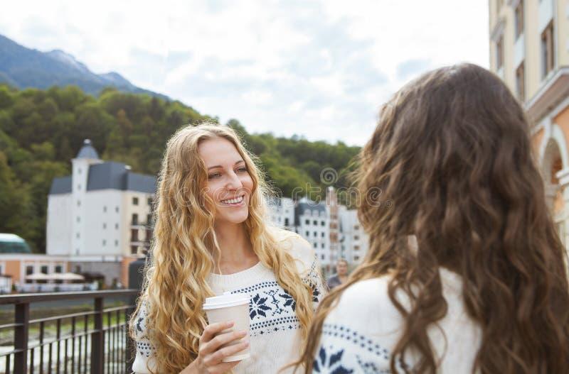 Duas mulheres felizes ocasionais que têm uma conversação na cidade fotos de stock
