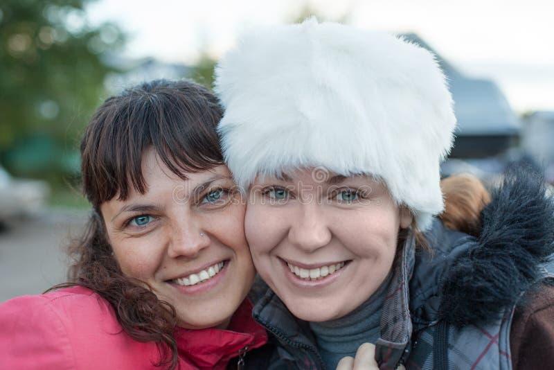 Duas mulheres felizes que abraçam, mordente de inclinação ao mordente e sorrindo, retrato facial fotos de stock royalty free