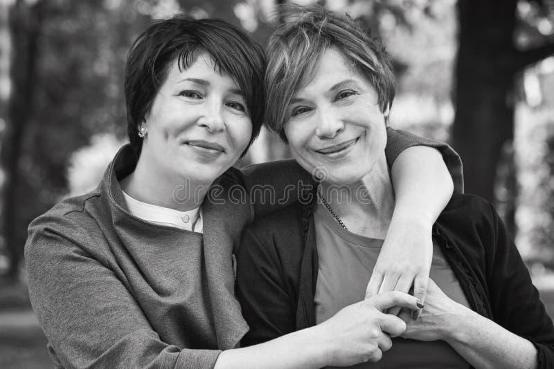 Duas mulheres felizes que abraçam no parque do verão, retrato preto e branco retro fotografia de stock royalty free