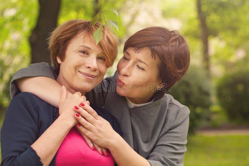 Duas mulheres felizes que andam no parque do verão, retrato fotografia de stock