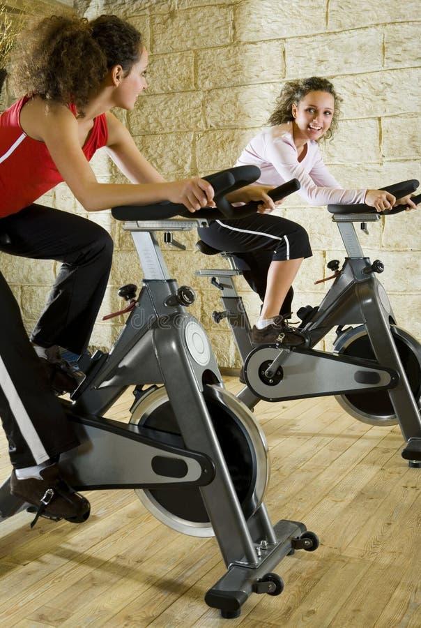 Duas mulheres felizes que elaboram em bicicletas de exercício fotos de stock