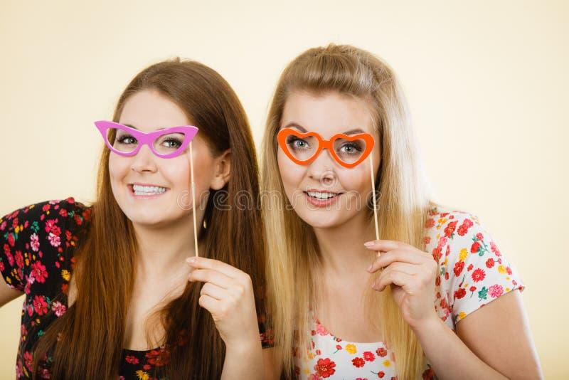 Duas mulheres felizes que guardam monóculos falsificados na vara imagem de stock royalty free