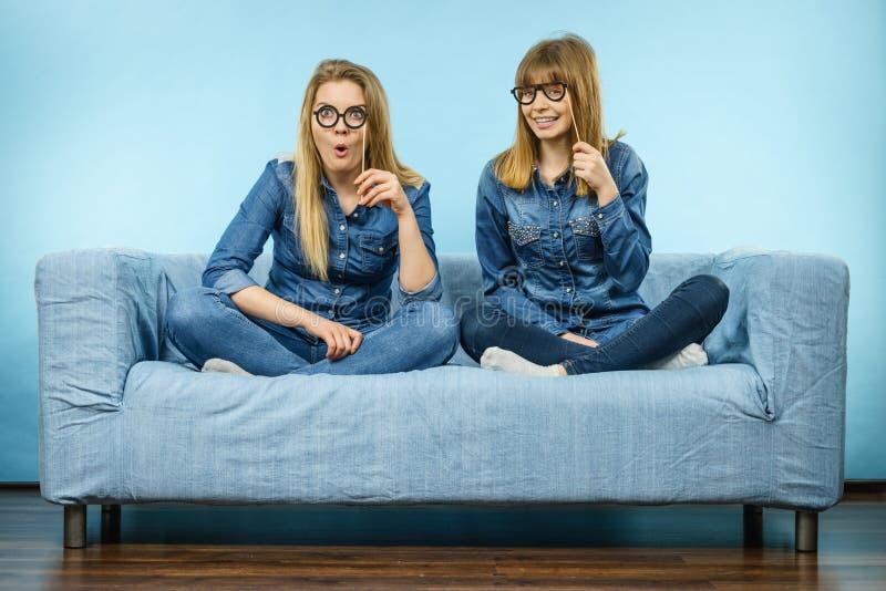 Duas mulheres felizes que guardam monóculos falsificados na vara imagens de stock royalty free