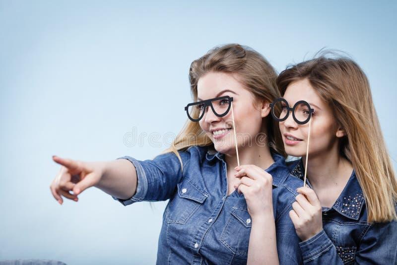 Duas mulheres felizes que guardam mon?culos falsificados na vara imagem de stock royalty free