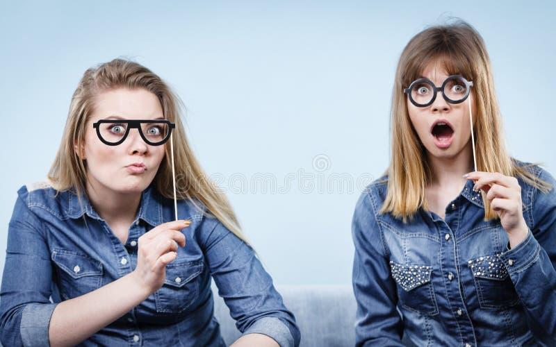 Duas mulheres felizes que guardam mon?culos falsificados na vara fotos de stock