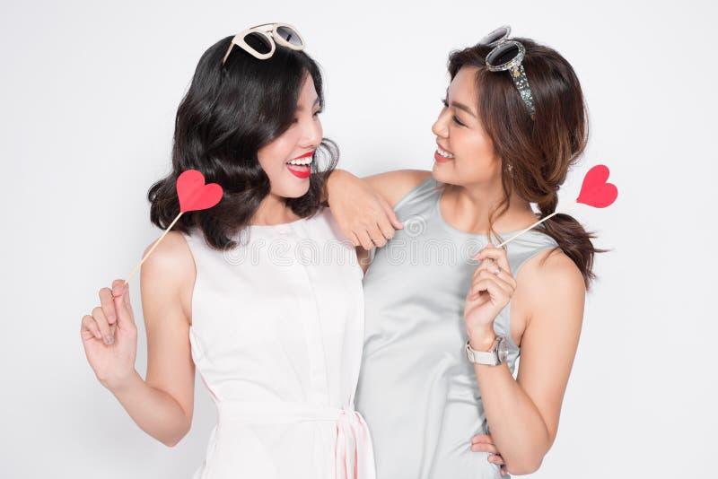Duas mulheres felizes que guardam o coração na vara que tem o dresse vestindo do divertimento foto de stock royalty free