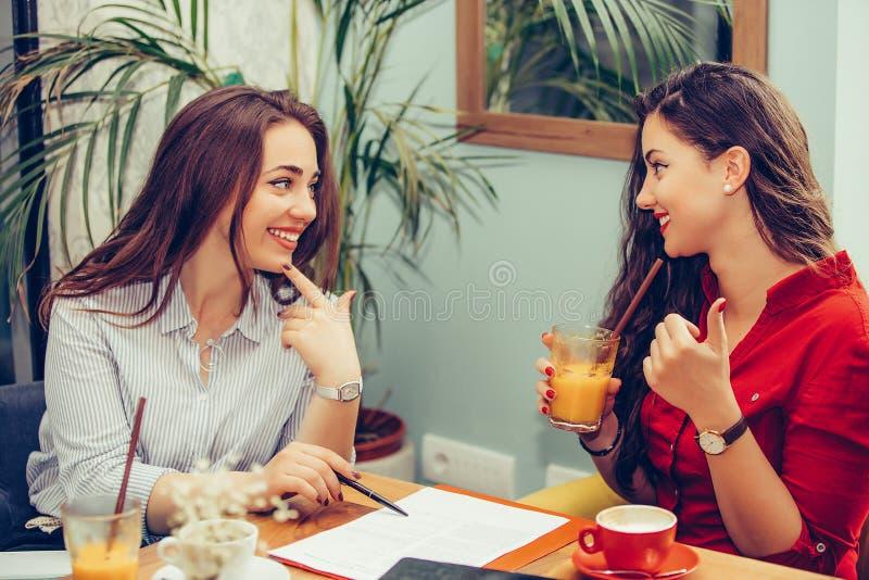 Duas mulheres felizes que leem documentos junto, apontando onde assinar um contrato fotos de stock