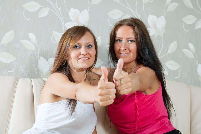 Duas mulheres felizes que mostram o polegar acima fotografia de stock royalty free