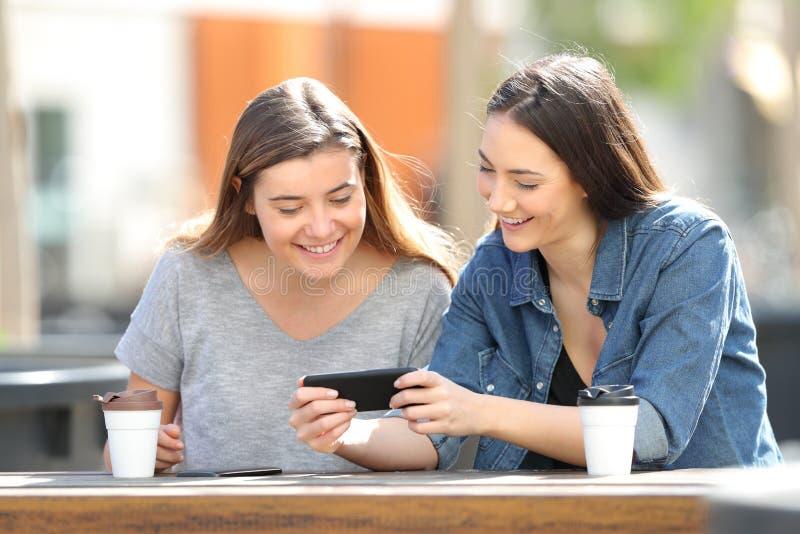 Duas mulheres felizes que olham meios no smartphone foto de stock