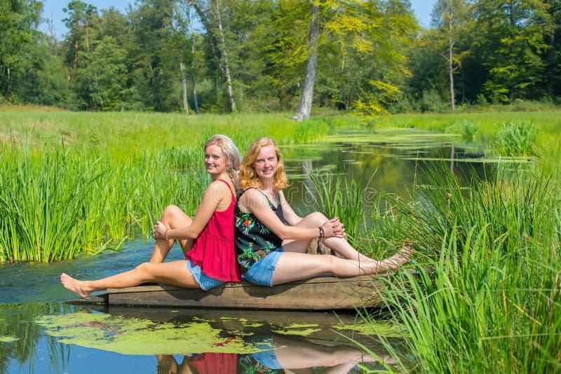 Duas mulheres holandesas novas sentam-se na água na natureza imagens de stock