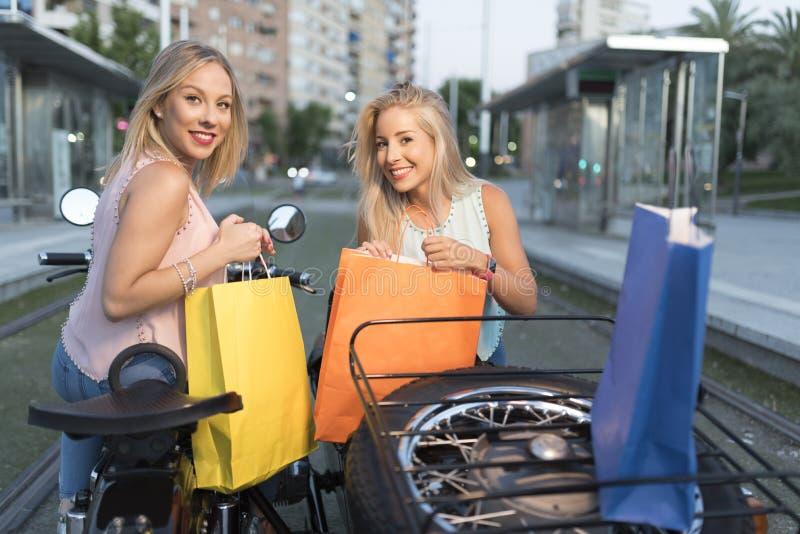 Duas mulheres louras da irmã feliz no side-car que olha sacos de compras imagens de stock