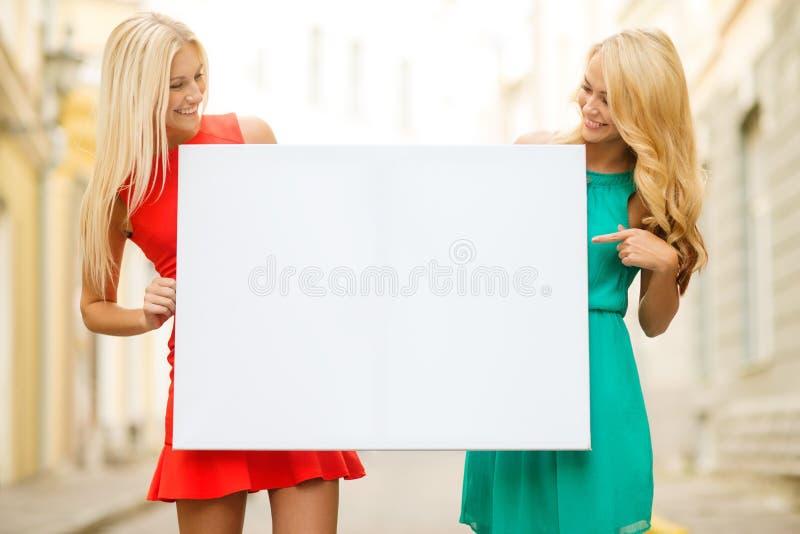 Duas mulheres louras felizes com placa branca vazia imagem de stock royalty free