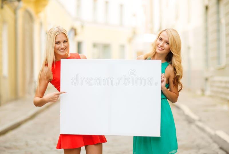 Duas mulheres louras felizes com placa branca vazia foto de stock