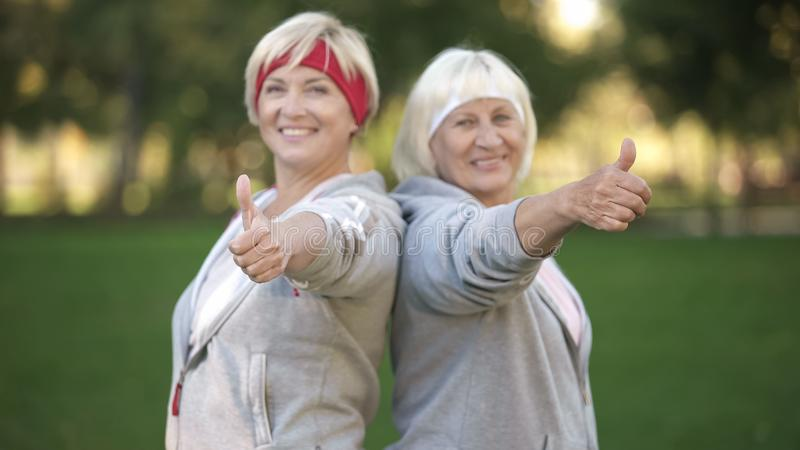 Duas mulheres maduras felizes que sorriem e que mostram os polegares acima no parque, estilo de vida saudável imagem de stock
