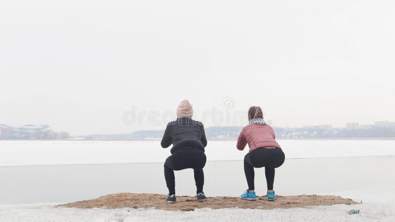 Duas mulheres magros que estão na praia nevado e que fazem ocupas fotografia de stock royalty free
