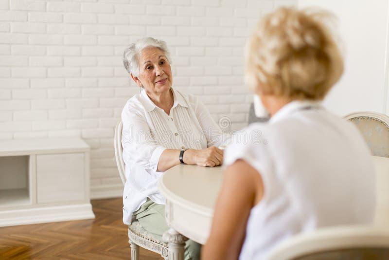 Duas mulheres mais idosas que bebem o coffe em casa e a fala imagens de stock royalty free