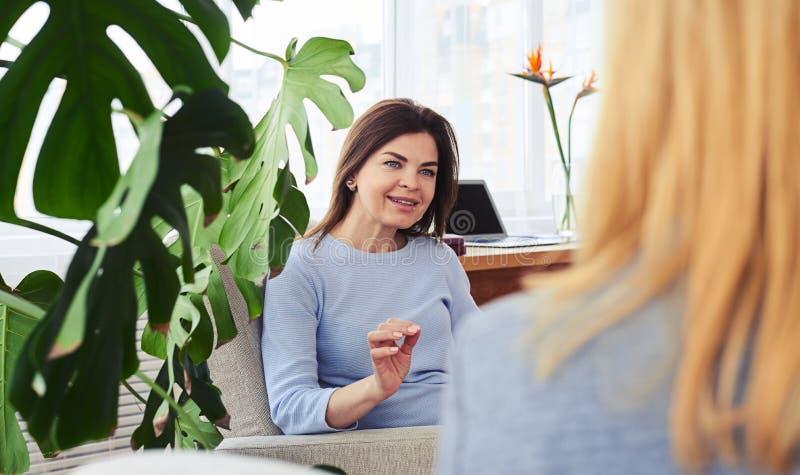 Duas mulheres maravilhosas que conversam ao beber o café em roo vivo imagens de stock