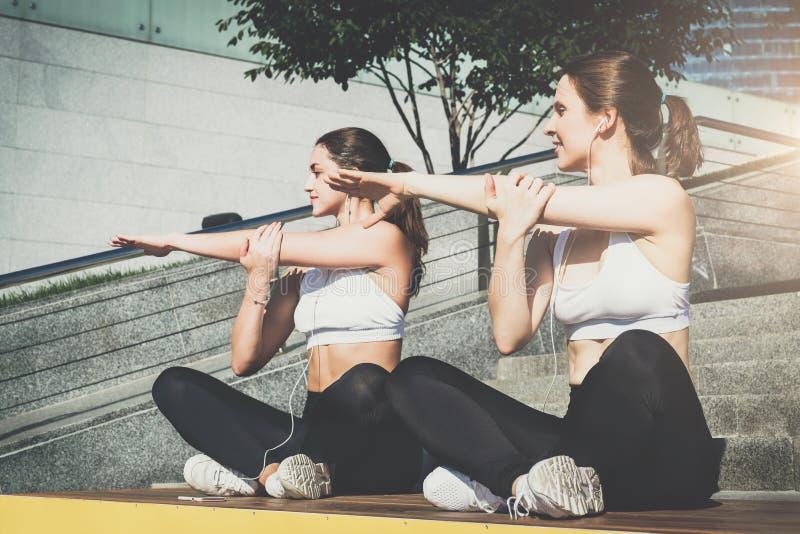 Duas mulheres, meninas no sportswear que faz o esticão exercitam ao escutar a música Exercício, deitando na rua da cidade foto de stock royalty free