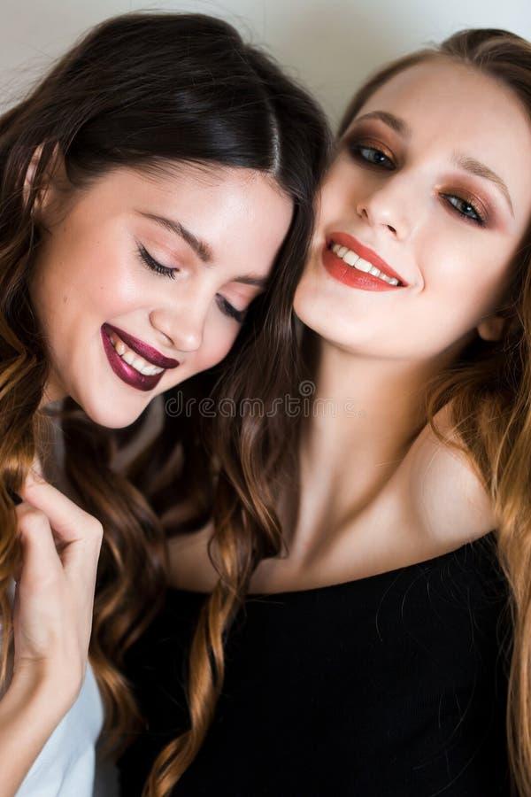 Duas mulheres morenos e louras bonitas, amigas com composição profissional olham a câmera com sorriso no fundo branco Alegria, imagens de stock royalty free