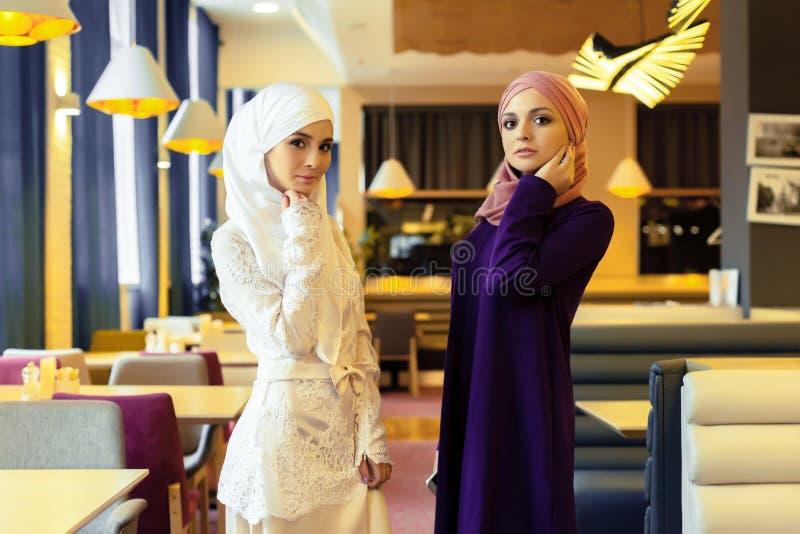 Duas mulheres muçulmanas bonitas na roupa oriental moderna fotos de stock