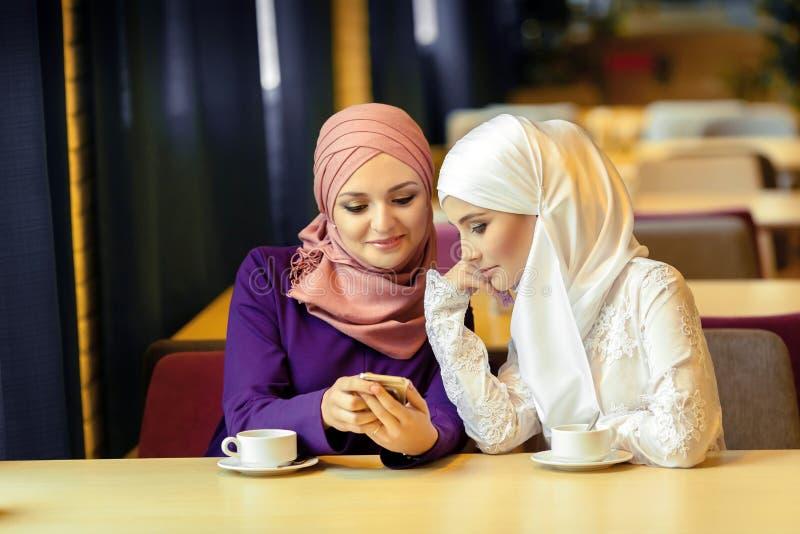 Duas mulheres muçulmanas novas que sentam-se em um café e que procuram algo em um telefone celular foto de stock