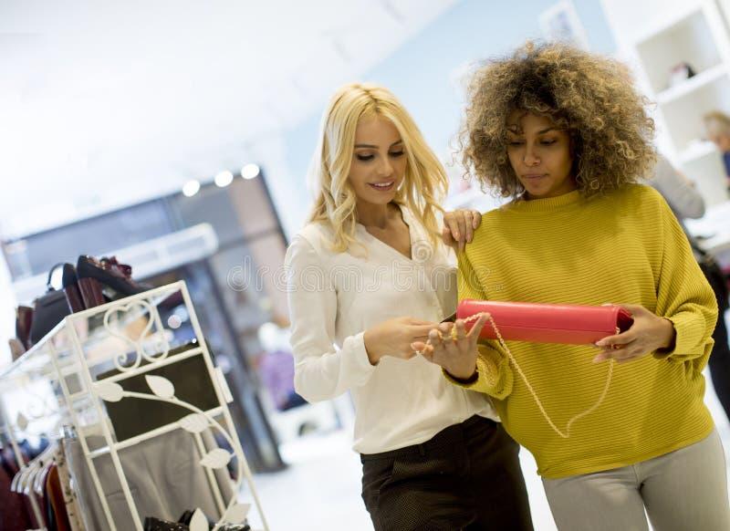 Duas mulheres multi-étnicos novas que compram a bolsa na loja fotos de stock royalty free
