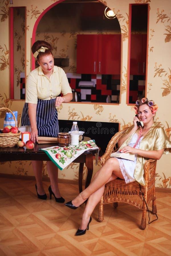 Duas mulheres na cozinha Trabalhe e relaxe, falando no telefone Cena do agregado familiar, estilo de vida imagens de stock