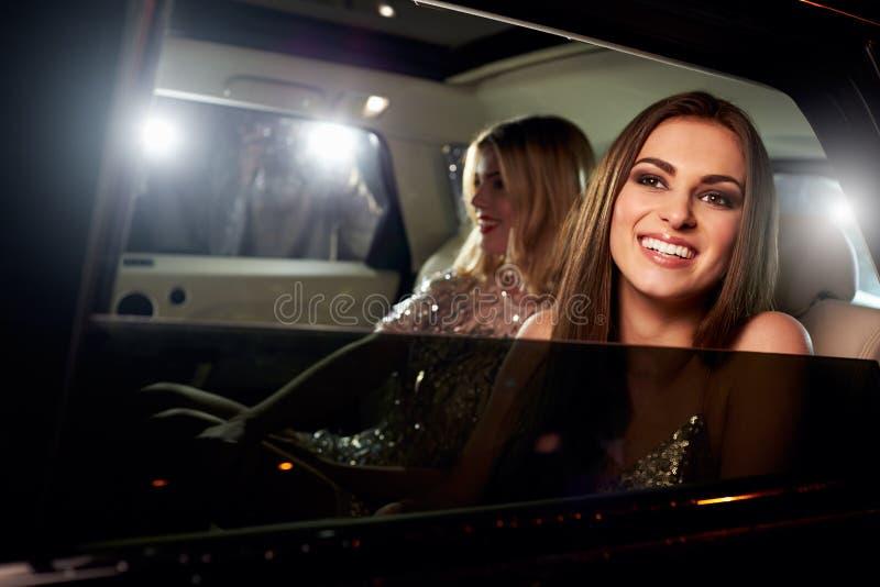 Duas mulheres na parte de trás de um limo, fotografado por paparazzi fotografia de stock