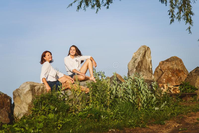 Duas mulheres nas camisas brancas sentam-se nas rochas na costa no dia ensolarado do verão fotos de stock