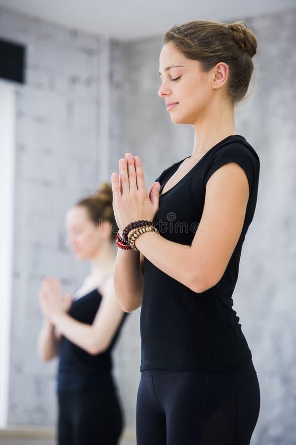 Duas mulheres no gym classificam, exercício do abrandamento ou classe da ioga fotos de stock royalty free