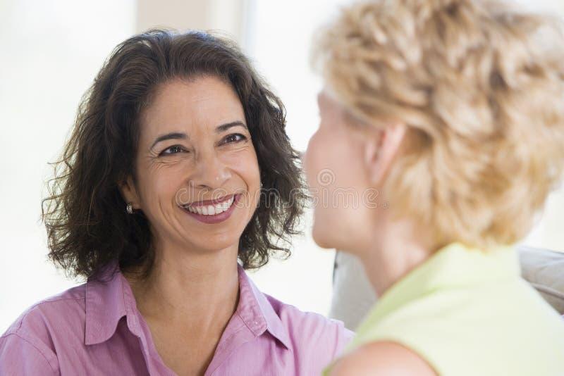 Duas mulheres no sorriso da sala de visitas fotografia de stock