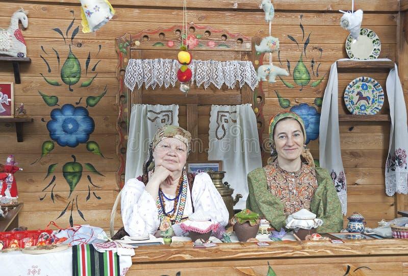 Duas mulheres no vestido nacional do russo, a de assento imagens de stock royalty free