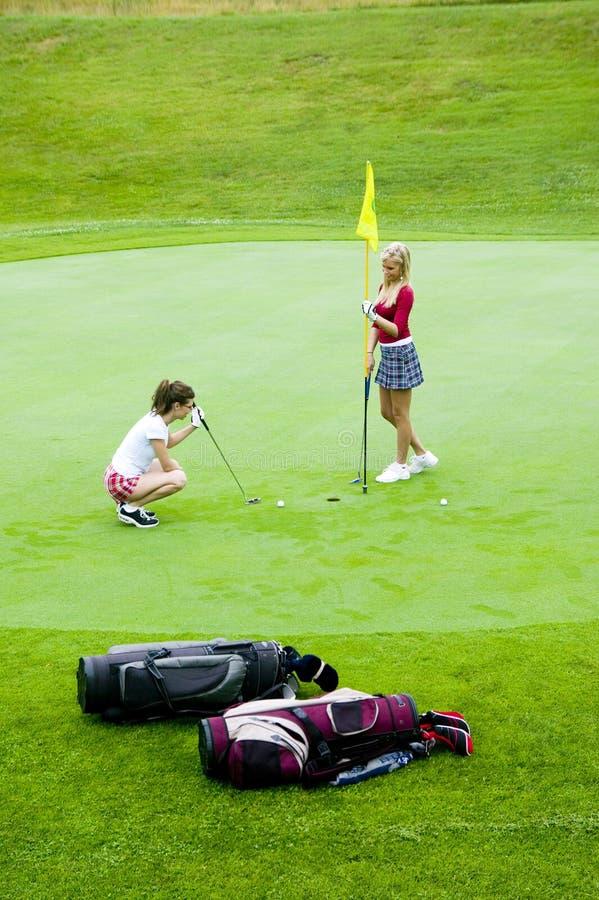 Duas mulheres novas apreciam um jogo do golfe. fotografia de stock royalty free