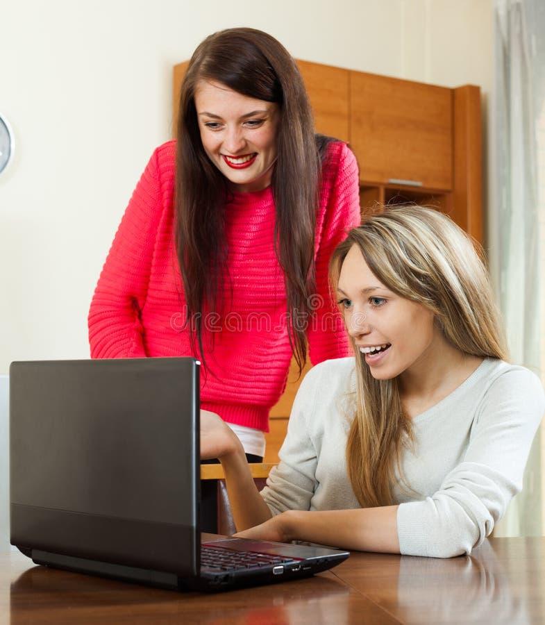 Duas mulheres novas com portátil fotografia de stock royalty free