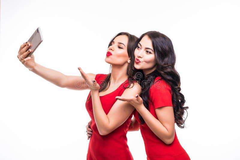 Duas mulheres novas da beleza que vestem o vestido vermelho que toma o selfie no fundo branco foto de stock royalty free