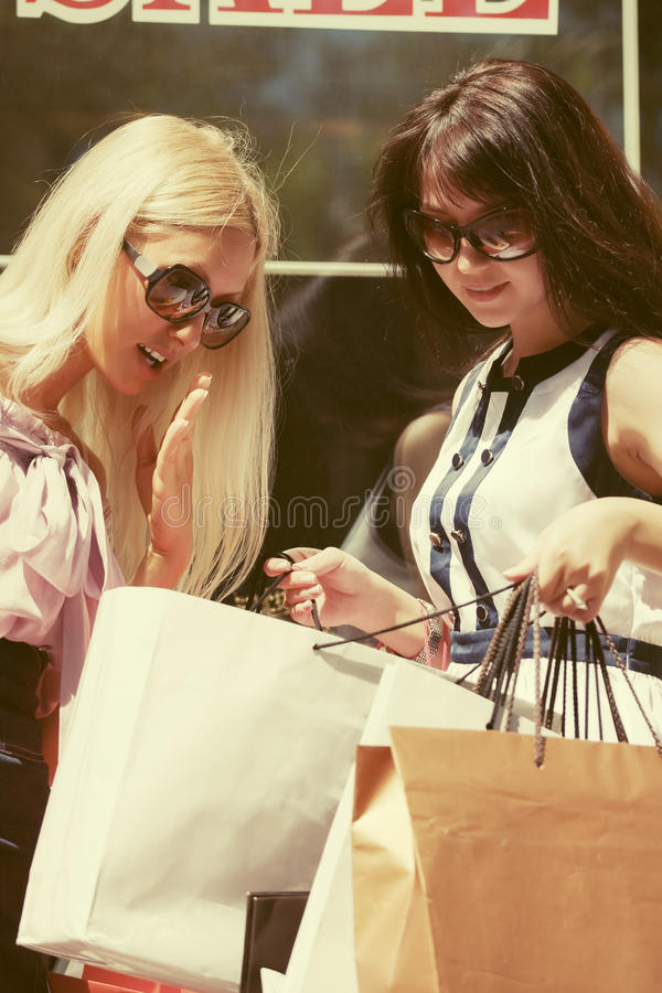 Duas mulheres novas da forma com os sacos de compras na alameda imagens de stock royalty free