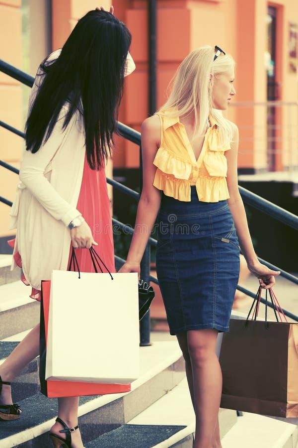 Duas mulheres novas da forma com os sacos de compras na alameda pisam foto de stock