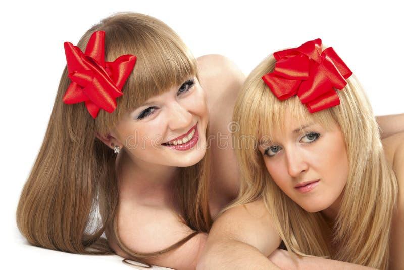 Duas mulheres novas de sorriso com curva vermelha do presente fotografia de stock royalty free