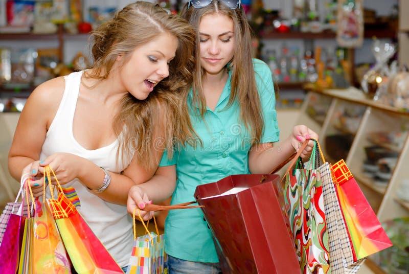 Duas mulheres novas excited felizes com sacos de compra imagem de stock royalty free